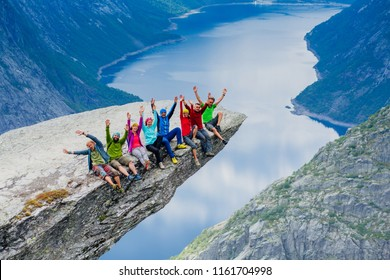 Happy young sportive people group of eight in bright colorful sportswear sitting with hands up and enjoy in Trolltinga Norway mountain. Full body portrait