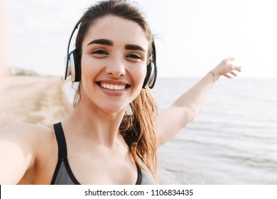 Happy young sportswoman with headphones taking a selfie with outstretched hands while standing at the beach and pointing away