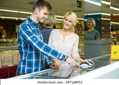 Happy young spouses buying frozen food in grocery store and smiling
