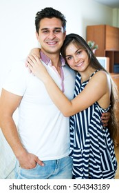 Happy young spouses posing and hugging in living room.Focus on the man
