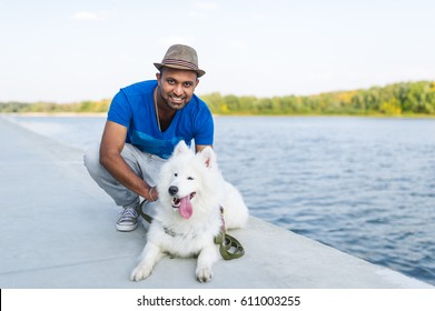 Happy young sri lankan man with her dog white samoyed sitting by the river. Cute young sri lankan man hugging white dog, smiling. Closeup. Selective focus in man.