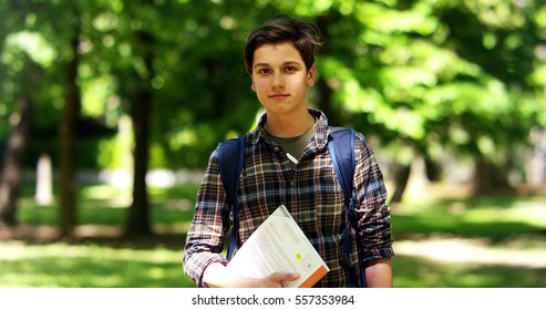 happy young student boy, on a sunny day at the park, reading a book and study and is very smiley in slow motion