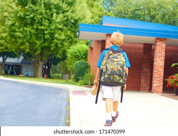 Happy young student going back to school carrying backpack. Cheerful school boy walking  to school building confidently. Color Image, copy space.