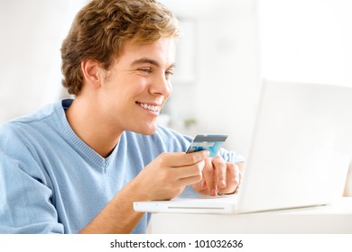 happy young student shopping online using credit card at home