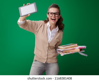 happy young student woman with books, notes and records and tablet PC showing the convenience of technology isolated on green