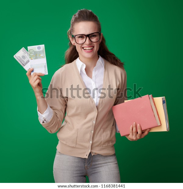 happy young student woman with books and money packs isolated on green
