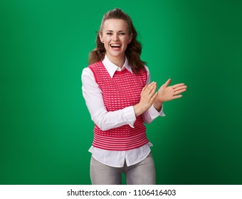 happy young student woman in a red waistcoat clapping isolated on green background