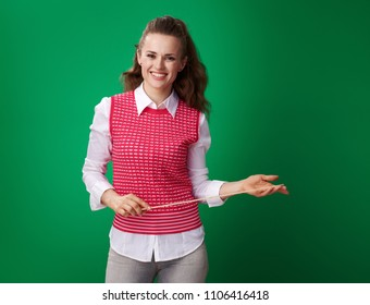 happy young student woman in a red waistcoat with a pointer against green background