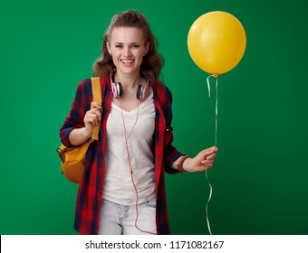 happy young student woman in a red shirt with backpack and headphones holding yellow balloon isolated on green background