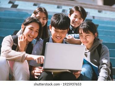 ノートパソコンを見て階段に座る幸せな若い学生