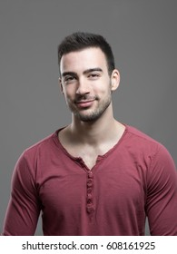 Happy young stylish stubble man smiling at camera over gray background