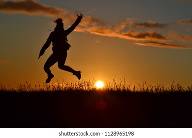 Happy young succesfull woman silhouette jumping with the hands up in the orange sunset. Celebrating winning. Enjoying summer in the mountains. Outdoor scenery. Freedom,  active lifestyle concept.