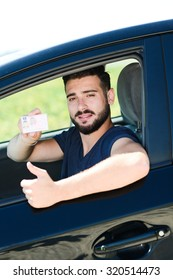 happy young successful man showing his new european driving license