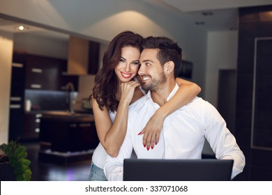 Happy young successful manager couple at home with laptop, confident people