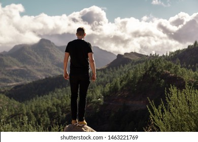 Happy young tall man from behind standing and enjoying life in the mountains of gran canaria, canary islands, spain