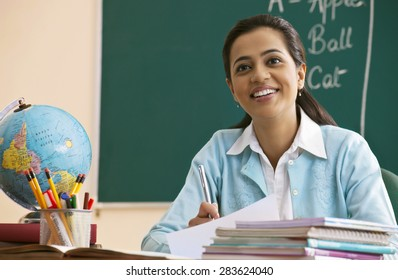 Happy young teacher looking away at desk
