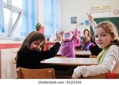 happy young teacher woman at elementary school teaching and giving lessons to group of young smart children