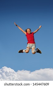 Happy young teenage girl child jumping against blue sky with white clouds background.