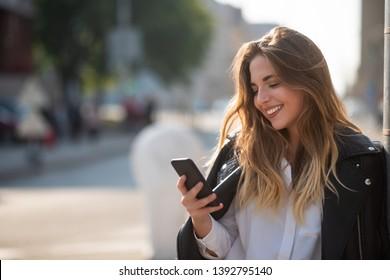 Happy young teenage girl holding phone, bokeh effect.