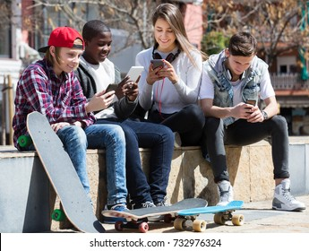 Happy young teenage males and girls relaxing with mobile phones outdoor