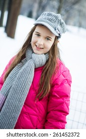 A happy young teenager dressed for winter in the snow in central park New York