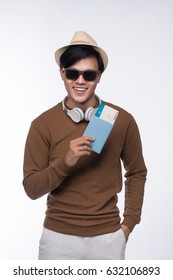 Happy young tourist asian man holding passport over grey background