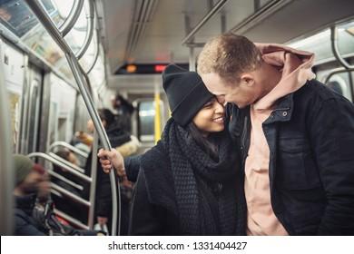 Happy young tourist couple in New York City subway train travel around
