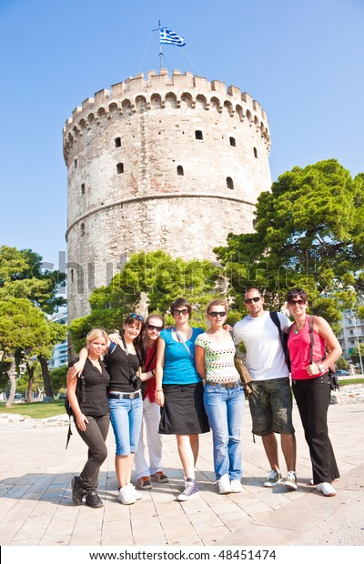 happy young tourist in front of white tower in Greece