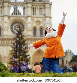 Happy young tourist in Paris on a winter day, main Parisian Christmas tree and Notre-Dame cathedral in the background