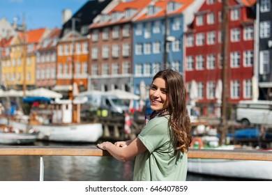 Happy young tourist woman smiling at camera, sitting at the Nyhavn harbor pier Copenhagen, Denmark. Visiting Scandinavia, famous European destination.