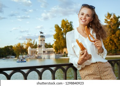 happy young tourist woman in white blouse and shorts at El Retiro Park in Madrid, Spain eating traditional Spain churro. churros - classic Madrid sweet snack. having micro holidays. european woman.
