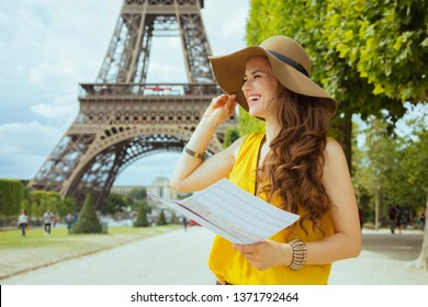 happy young tourist woman in yellow blouse and hat with map having excursion in the front of Eiffel tower in Paris, France.