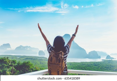 Happy young traveler woman backpacker raised arm up to sky enjoying a beautiful of nature at top of mountain view point and sea,Freedom wanderlust,Khao Samed Nang Chee Viewpoint,Phang Nga,Thailand