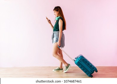 Happy Young Traveler Woman Walking with Suitcase and Music Headphone, Face looking at Smartphone and Smiling, Colorful Pastel Wall as background, Full Length, Side view