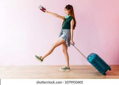 Happy Young Traveler Woman Walking with Suitcase and Music Headphone, Face looking up and Smiling, Colorful Pastel Wall as background, Full Length, Side view