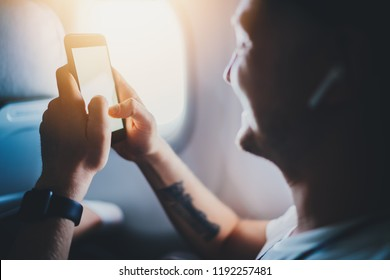 Happy young traveller man sitting in airplane and typing sms message, smiling hipster guy listening to music in earphones and using modern smartphone, business travel or vacation concept, flare light