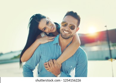 Happy young trendy couple smiling piggyback pose at oudoors