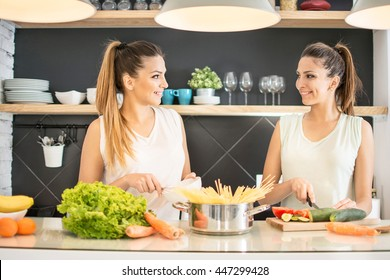 Happy young twin sisters preparing organic vegetables salad for lunch together in the kitchen.