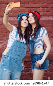 Happy young twins girls doing selfie. Wearing bright bandanas and denim overalls. On a brick urban wall background.