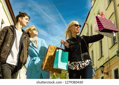 Happy Young two business girls blondes in glasses and a brunet guy walk down the street and enjoy shopping, shopping bags, gifts in their hands. Consumerism, shopping, lifestyle concept.