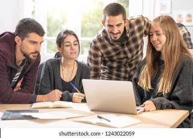 Happy young university students studying with laptop in library. Group of multiracial people in college library sitting together at table with books and laptop. Happy young people.