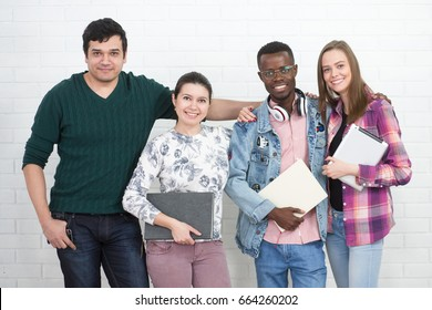 Happy young university students studying with books in library. Group of multiracial people in colleg