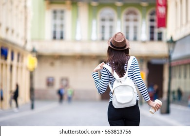 Happy young urban woman drinking coffee in european city. Travel tourist woman with hot drink in Prague outdoors during holidays in Europe.