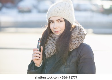 Happy young vaper girl with vaporizer gadget.very popular vaping device to smoke ejuice.Pretty white model smokes ejuice
