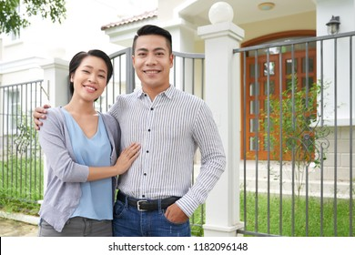 Happy young Vietnamese couple standing in front of their new house