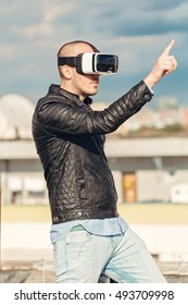 Happy young wearing a pair of VR glasses and pointing with his finger to the blue sky background on the rooftop building excited by augmented reality cityscape