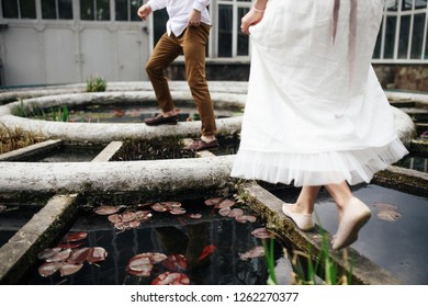 Happy young wedding couple walks on the old fountain in the garden