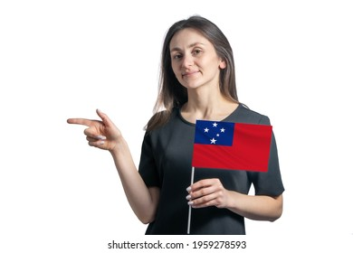 Happy young white woman holding flag Samoa and points to the left isolated on a white background.