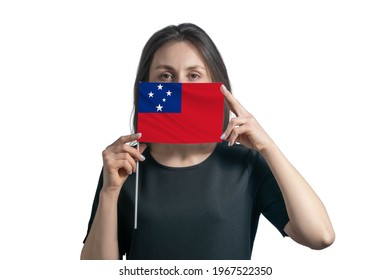 Happy young white woman holding flag Samoa flag and covers her face with it isolated on a white background.