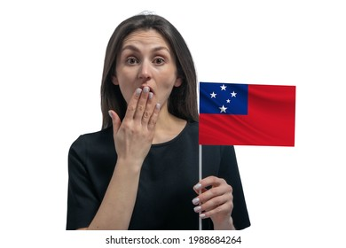 Happy young white woman holding flag of Samoa and covers her mouth with her hand isolated on a white background.